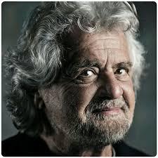 L'immagine mostra l'ex-comico e fondatore del Movimento 5 Stelle Beppe Grillo. Un uomo dai capelli bianchi e mossi sebbene corti con un accenno di barba bianca. La foto è a colori desaturati