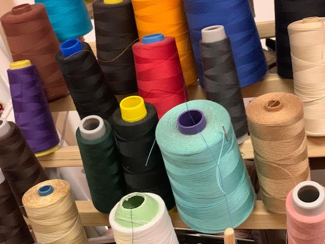 Rocchetti di filo per macchina per cucire di vari colori, all'interno del laboratorio dell'Associazione Spazio3R