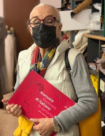 Una donna tiene in mano il manuale illustrato di italiano in sartoria, all'interno del laboratorio sartoriale dell'Associazione Spazio3R