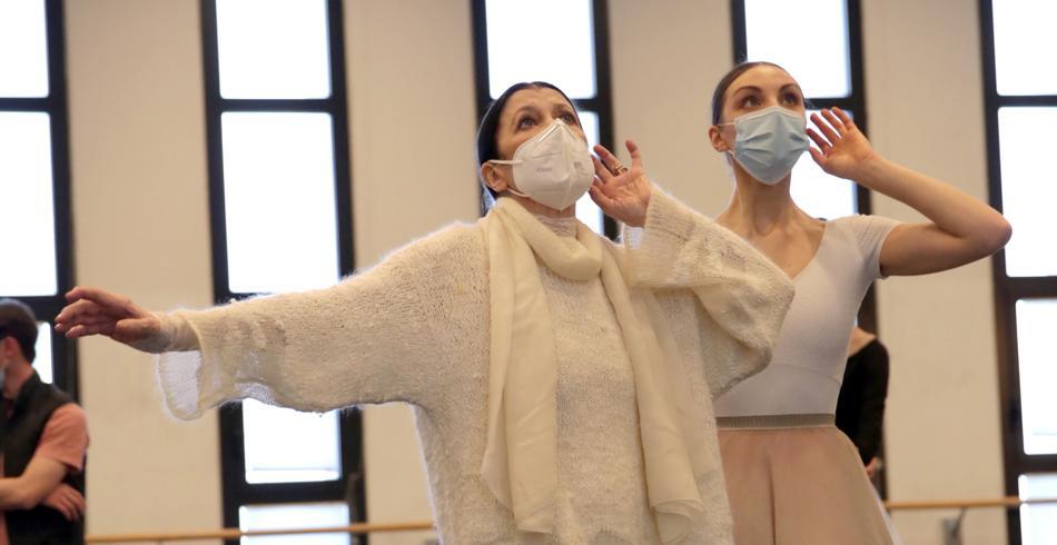 due figure femminili con una mascherina sul volto e vestite di bianco avvicinano il braccio sinistro all'orecchio