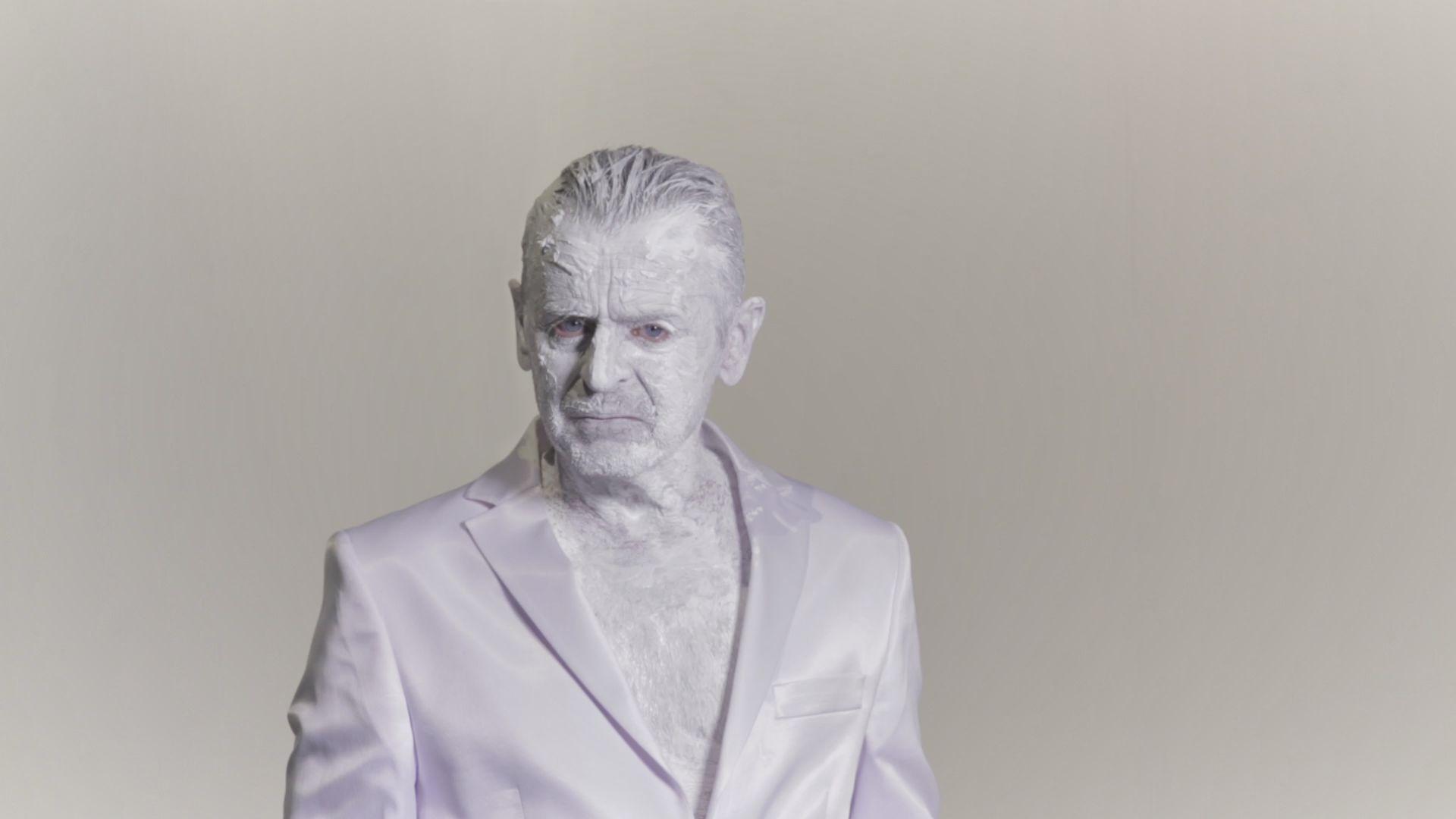 la foto in bianco e nero mostra un uomo con il volto ricoperto di bianco che indossa una giacca bianca e lurex