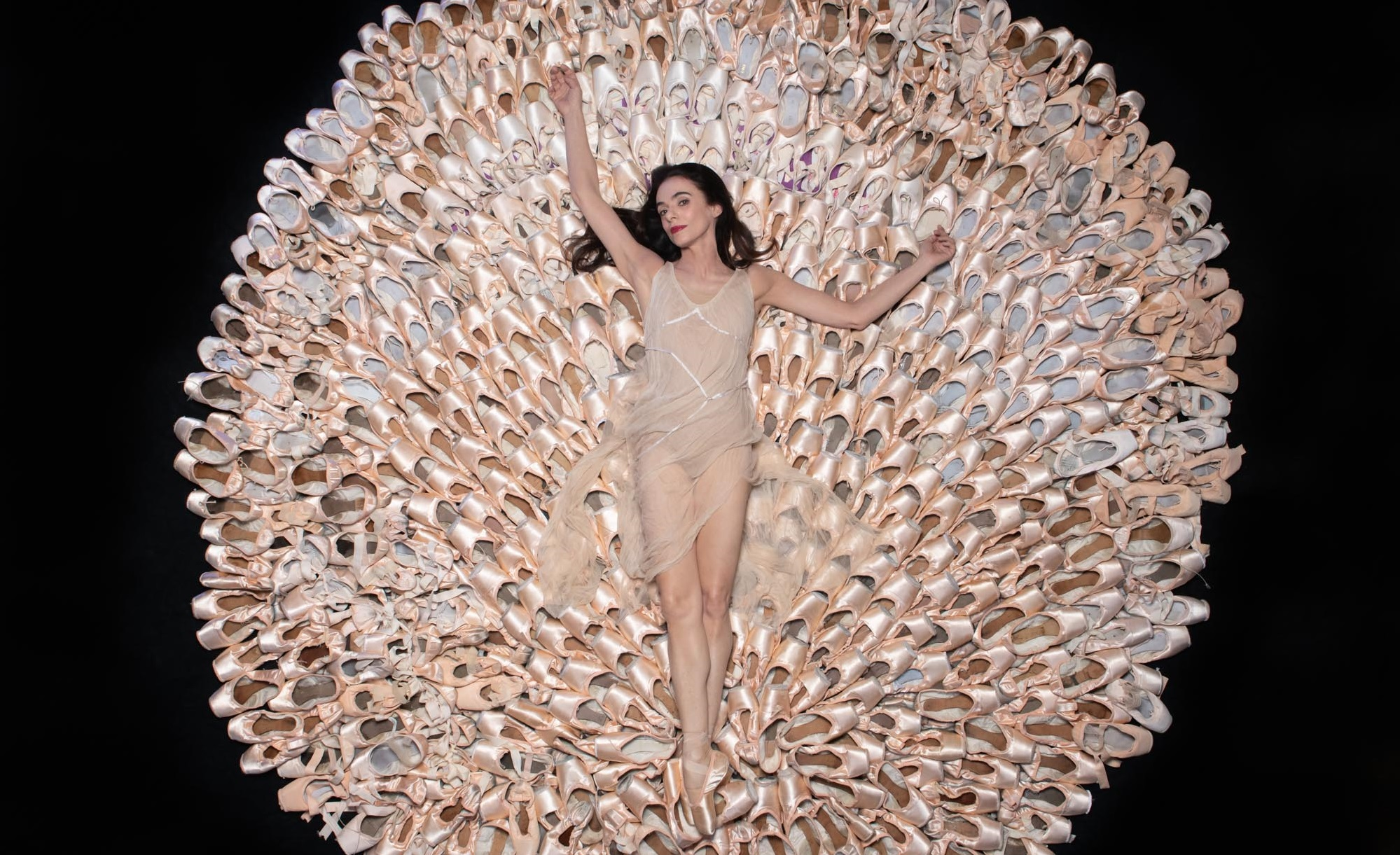 la foto a colori mostra la ballerina Alessandra Ferri sdraiata su un tappeto di scarpette da ballo rosa a forma di cerchio
