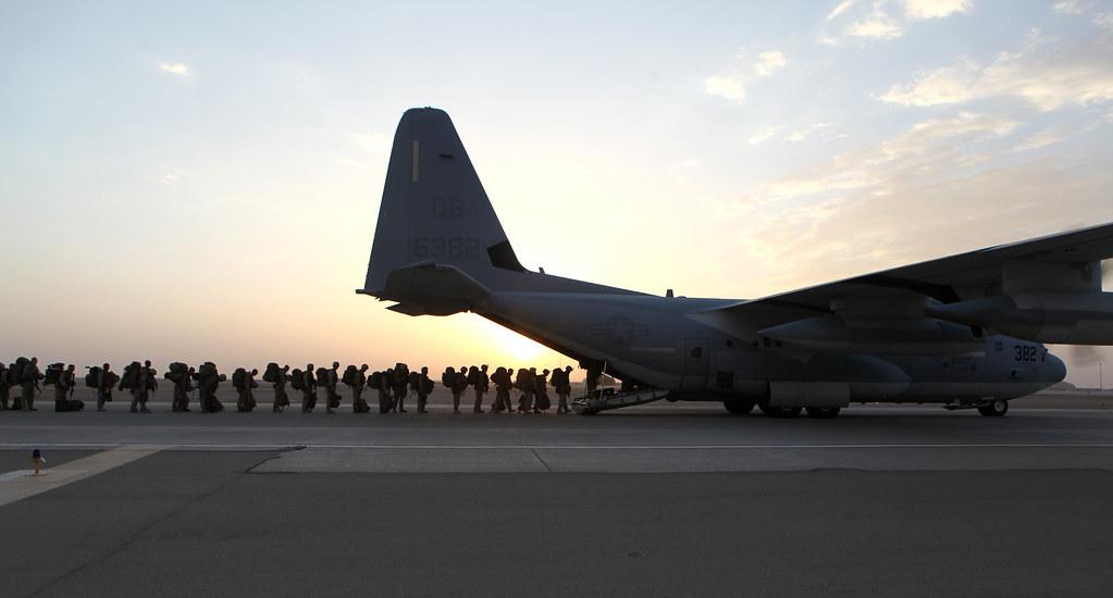 la foto a colori mostra un aereo militare con militari in fila che stanno per entrare; la foto è stata scattata all'alba o al tramonto
