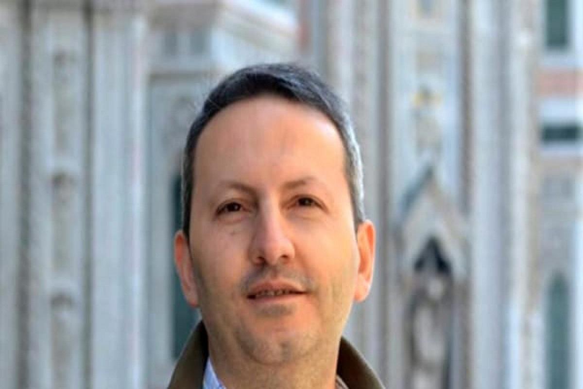 la foto a colori mostra un uomo in primo piano con i capelli un po' bianchi e gli occhi scuri