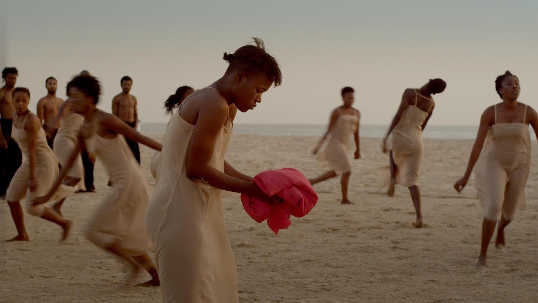 la foto a colori mostra alcune danzatrici di colore vestite di bianco; una di loro ha sulle mani un pezzo di stoffa rosso