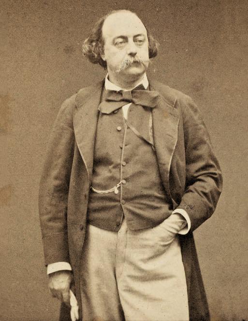 il dipinto in bianco e nero mostra un ritratto dello scrittore Gustave Flaubert, che indossa giacca e gilet scuri, pantaloni chiari, papillon e un guanto sulla mano destra