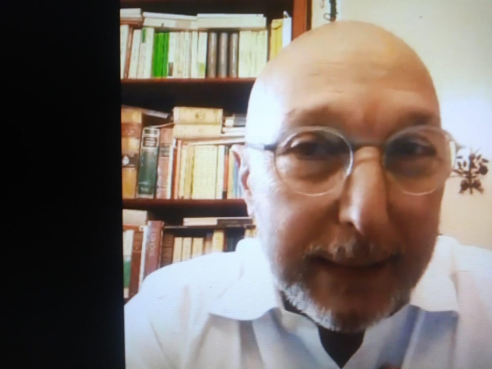 foto del poeta Fabrizio Sapio che, in primo piano, indossa barba, occhiali dalla montatura trasparente e camicia bianca.