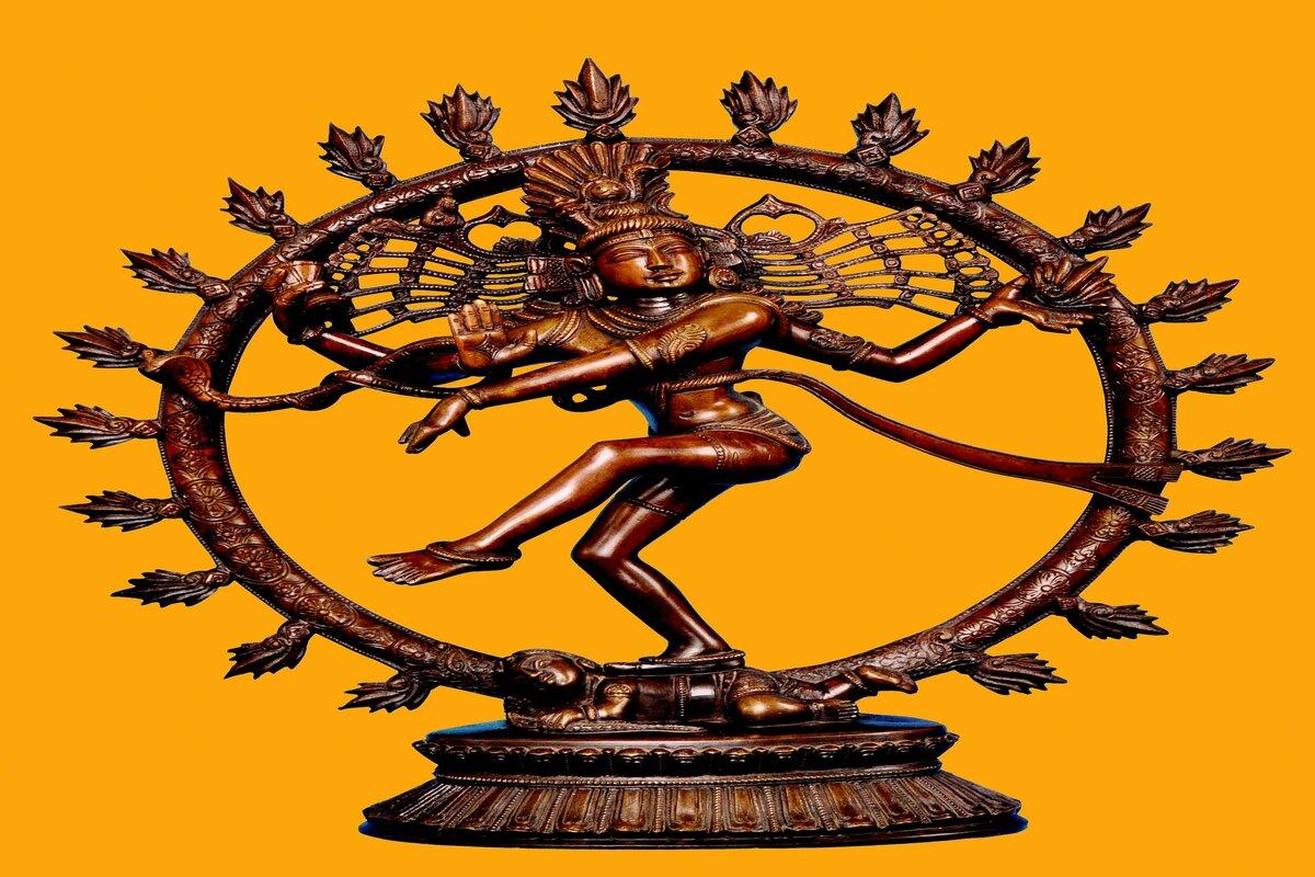 """l'immagine mostra una statua di una divinità induista Shiva nella tipica posizione della """"Danza continua"""". La figura è in equilibrio su un solo piede ed ha 4 braccia. E' circondata da una corona di fiammelle che la racchiudono in una sorta di guscio"""