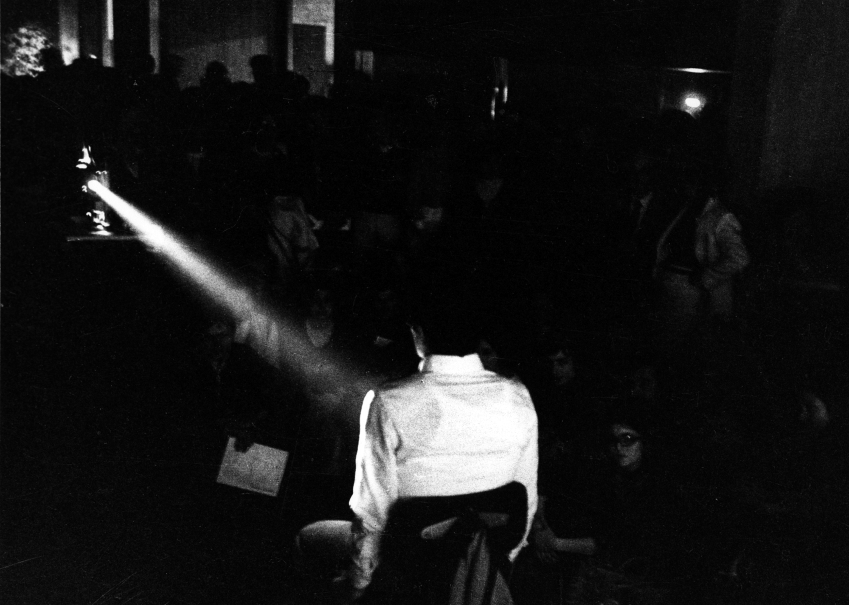 la foto in bianco e nero mostra un uomo girato di spalle che proietta un film di Pasolini
