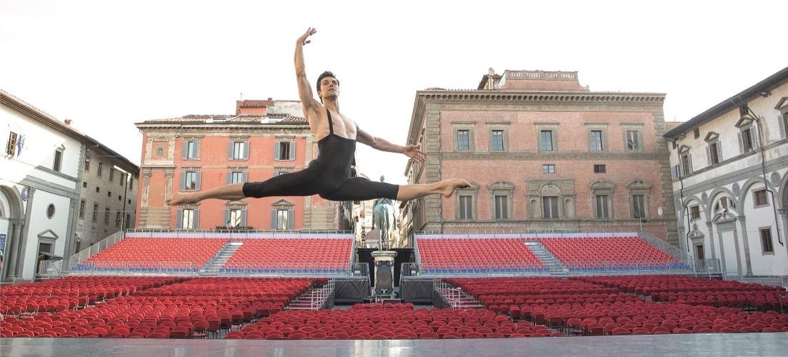 la foto a colori mostra il ballerino Roberto Bolle che esegue una spaccata in aria all'aperto in un teatro vuoto di giorno