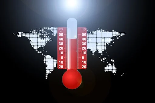foto a colori di un mappamondo con, al centro, un termometro che segna le elevate temperature atmosferiche di colore rosso