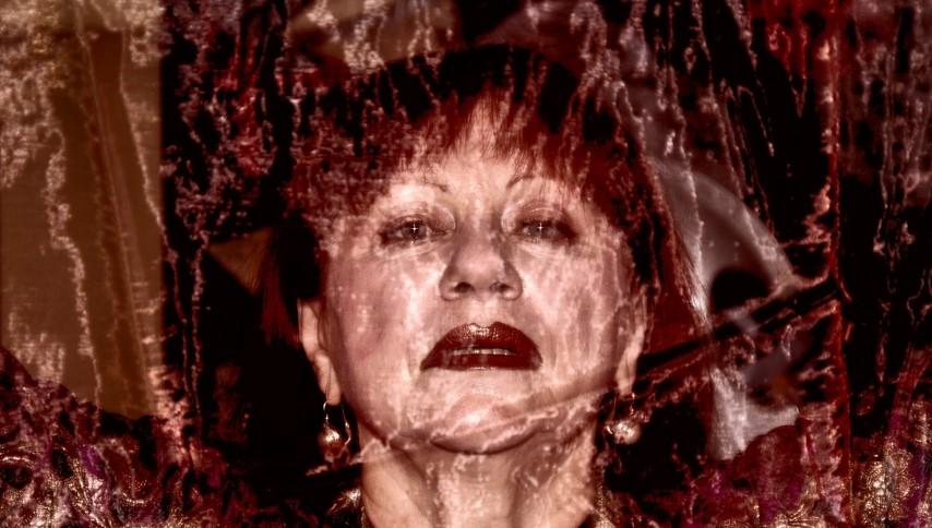 la foto a colori un po' sgranata mostra la testa dell'artista Evelina Schatz che indossa orecchini e un rossetto rosso