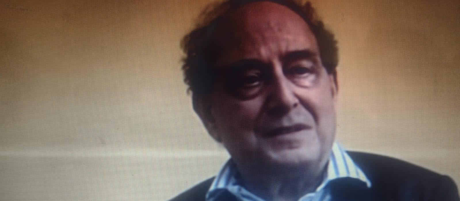 la foto a colori mostra lo scrittore Roberto Calasso a mezzobusto che indossa una giacca e gilet blu e camicia bianca a righe blu