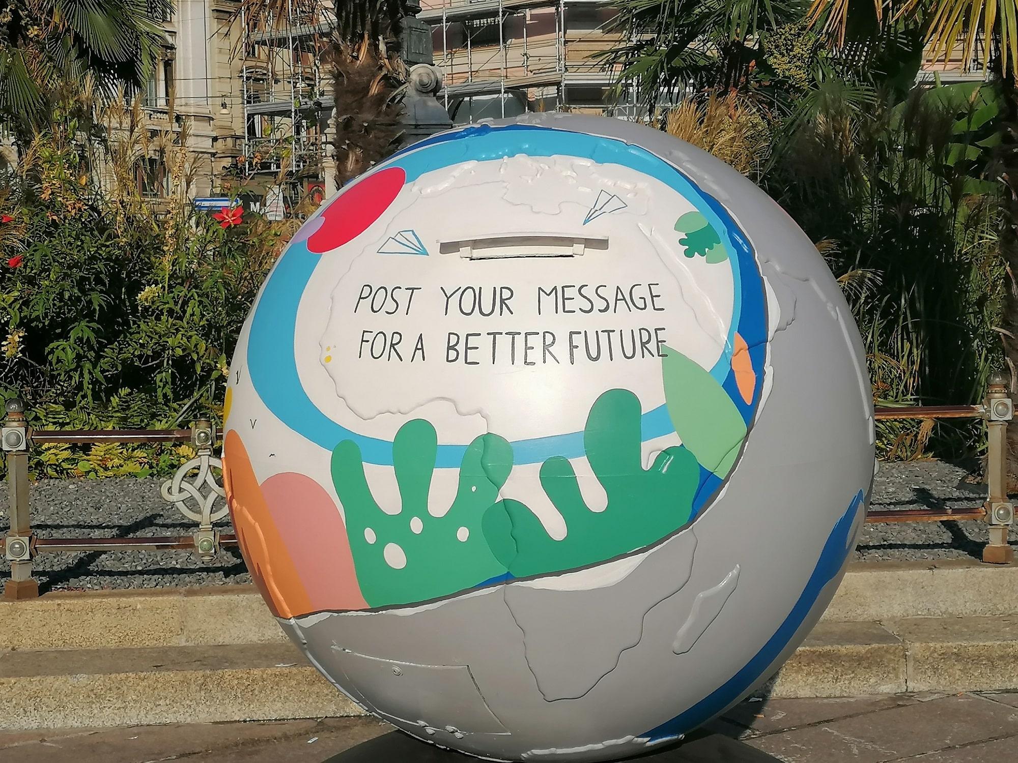 """su un oggetto dalla forma tonda leggiamo la scritta """"post your message for a better future"""". Sopra la scritta si apre una fenditura"""
