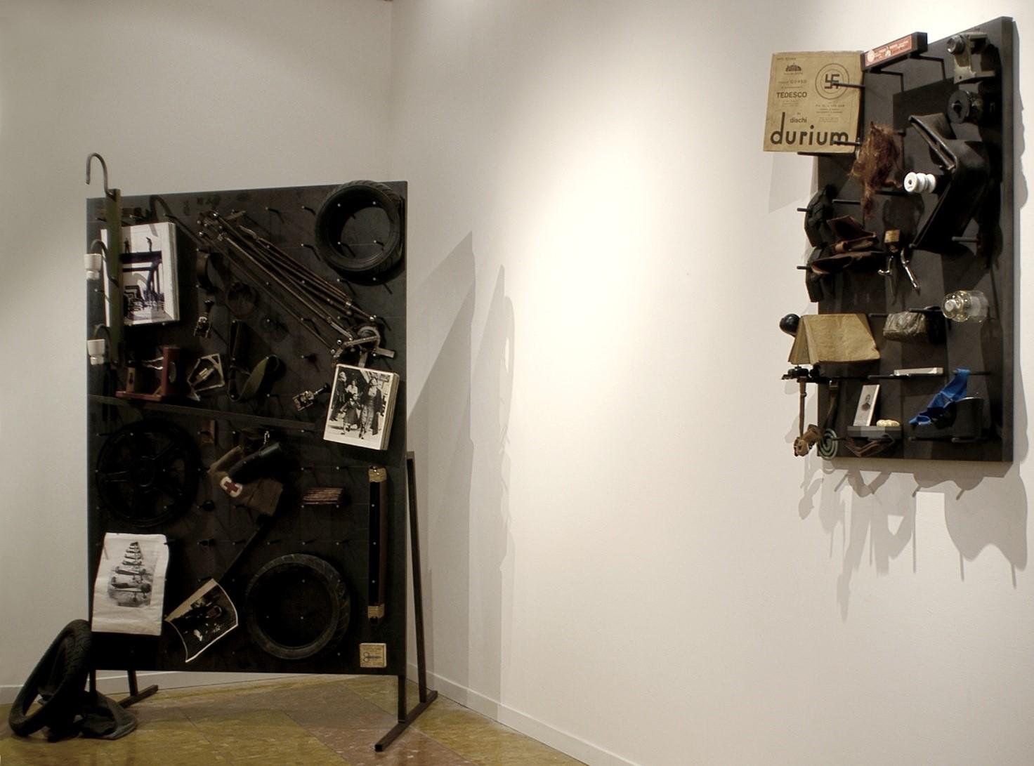 """L'immagine mostra un'opera di Fabio Mauri chiamata """"Mia Cugina Marcella"""", un pannello di ferro su cui sono attaccati vari oggetti di ferro e non"""